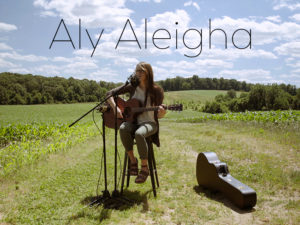 Aly Aleigha playing guitar in field with blue skies