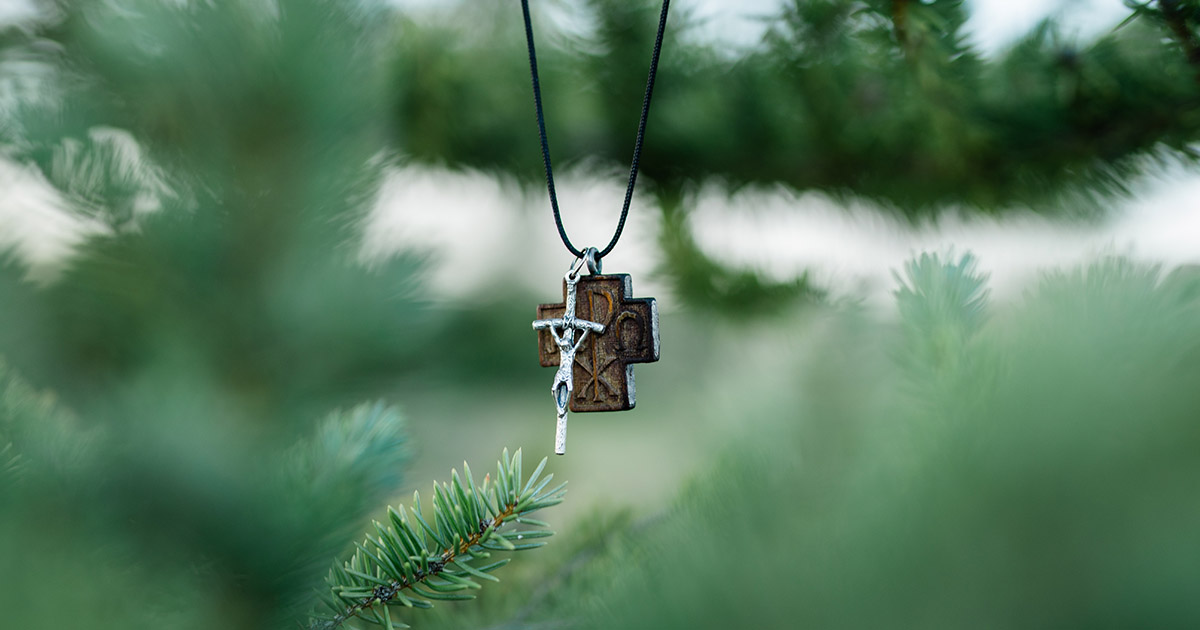 cross necklace hangs on tree branch