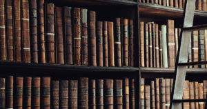 library shelf with old brown books
